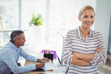 Portrait of smiling graphic designer standing with arms crossed in office