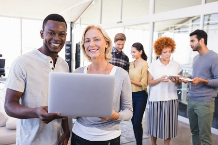 businesswear: Portrait of smiling business people holding laptop with colleagues using tablet pc in background