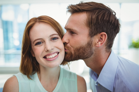 Affectionate man kissing woman in office Stock Photo