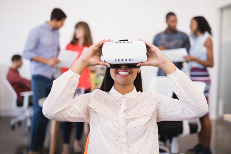 businesswear: Businesswoman using vr glasses with colleagues in background