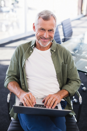 Portrait of smiling businessman using laptop while sitting on chair in office