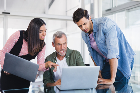 businesswear: Business people discussing over laptops at desk in office Stock Photo