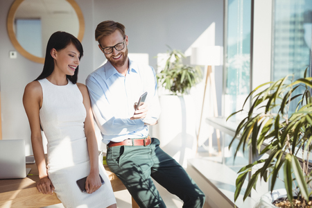 Happy executives using mobile phone at desk in office