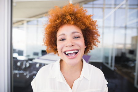 Close up portrait of businesswoman laughing in office Stock Photo