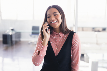 Smiling creative businesswoman talking on mobile phone at office Stock Photo