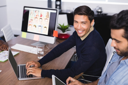 Portrait of happy businessman with colleague sitting at desk in office