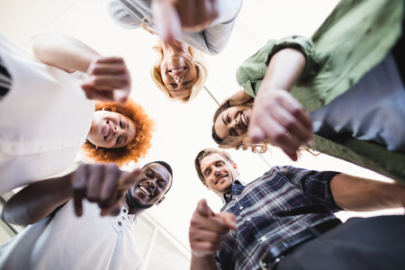 Directly below portrait of happy colleagues gesturing while standing against ceiling in office Stock Photo