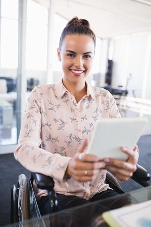 Portrait of smiling businesswoman using digital tablet while sitting on wheelchair at creative office