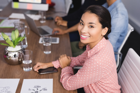 Portrait of businesswoman sitting at desk during meeting in office