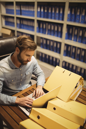 tensed: High angle view of businessman using laptop by files on table in storage room