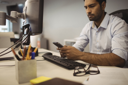 Businessman using mobile phone while sitting at desk in office