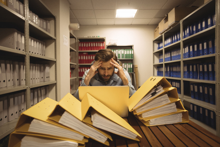 Worried businessman looking at laptop in file storage room