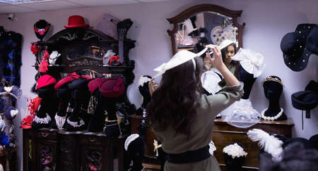 trial indoor: Woman selecting hat in jewelry section of boutique LANG_EVOIMAGES