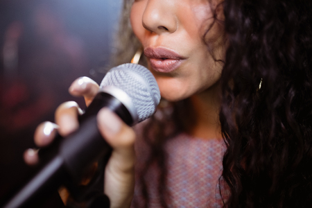 Close up of female singer singing at nightclub during music festival