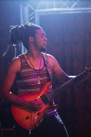 Guitarist playing guitar at nightclub during music concert