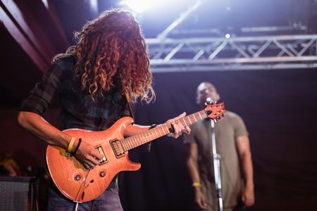 Male guitarist performing on stage at nightclub