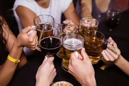 High angle view of friends toasting drinks at nightclub