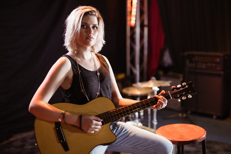 Portrait of female musician playing guitar while sitting on stool in nightclub