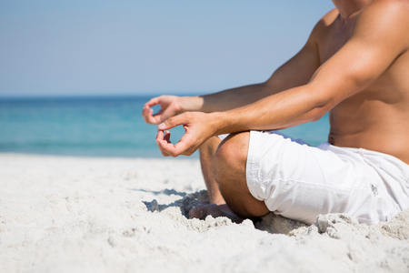 Low section of shirtless man meditating at beach on sunny day Stock Photo