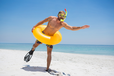 Man with snorkel wearing inflatable ring while standing at beach on sunny day