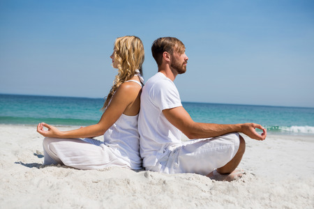 Side view of couple meditating while sitting back to back at beach
