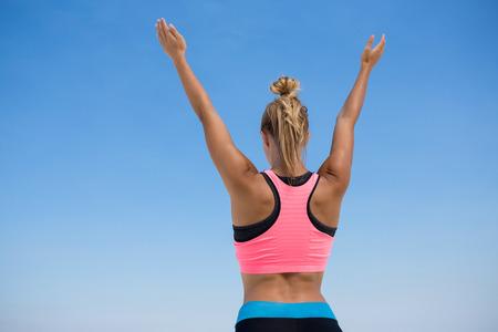 boca cerrada: Vista posterior de la mujer con los brazos levantados de pie contra el cielo azul claro