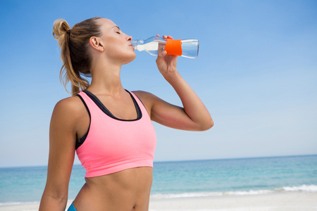 Woman drinking water while standing at beach against clear sky