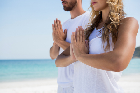 Midsection of couple exercising while standning at beach