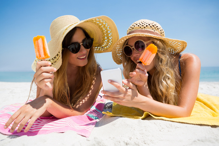 Female friends using smart phone while eating popsicles at beach