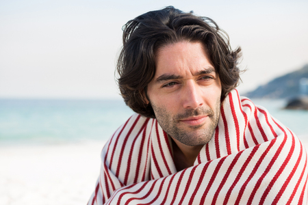 Close up of thoughtful man wrapped in shawl while sitting at beach on sunny day