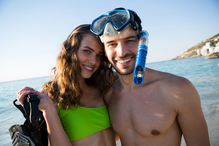 mujer mirando el horizonte: Portrait of smiling young couple with scuba mask at beach on sunny day