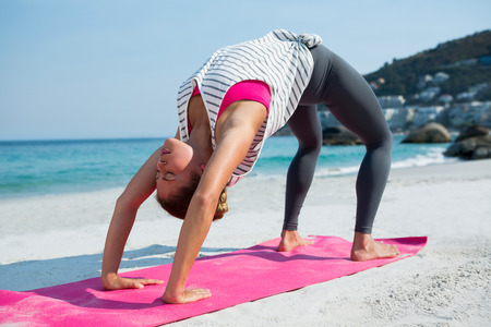 Full length of young woman practicing yoga in bridge position at beach on sunny day Stock Photo
