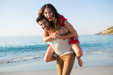 Portrait of young man piggybacking his cheerful girlfriend at beach on sunny day