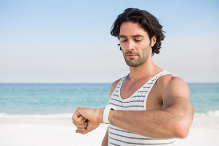 Man looking at wristwatch while against sea on sunny day Stock Photo