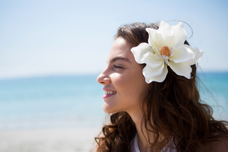 Side view of woman wearing flower while standing at beach on sunny day