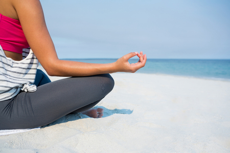 Low section of young woman meditating at beach against sky during sunny day