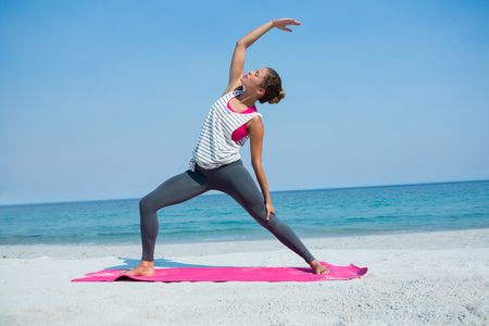 Full length of young woman exercising on mat at beach against clear blue sky Stock Photo