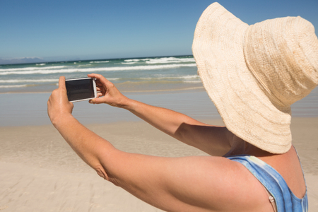 Side view of woman holding mobile phone while standing at beach on sunny day Stock Photo