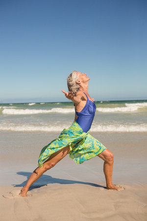 Side view of woman practising yoga while standing on shore at beach