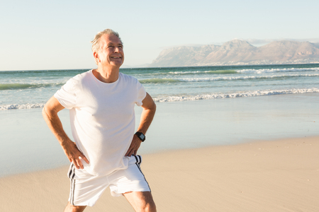 Smiling senior man exercising while standing on sand at beach