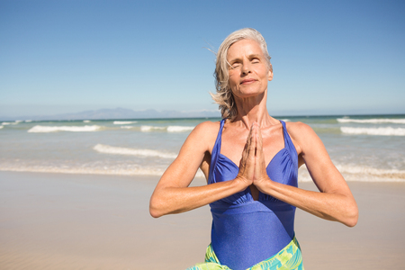 Close up of senior woman with hands clasped standing against clear sky at beach