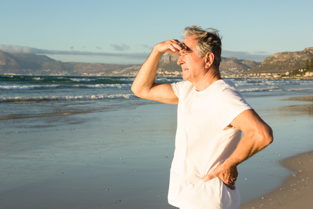 Senior man looking away while standing on shore at beach Stock Photo