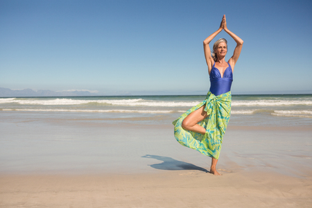 Senior woman practising yoga while standing against clear sky at beach Stock Photo