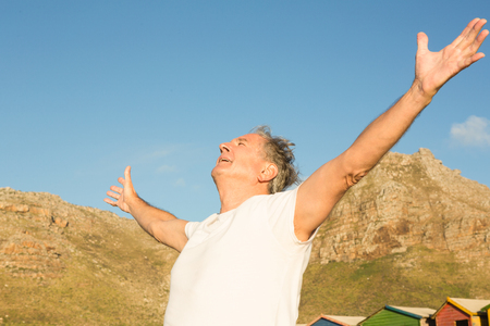 Close up of senior man with arms outstretched against clear sky