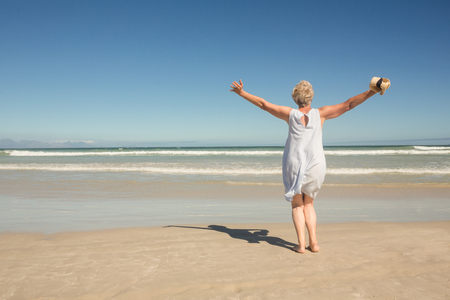 Rear view of woman standing on sand against clear sky at beach Stock Photo
