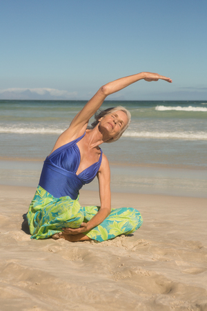 Close up of woman practising yoga while sitting on sand at beach Stock Photo