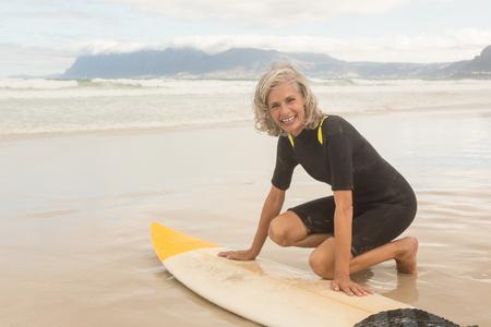 Portrait of smiling senior woman preparing for surfboarding at beach