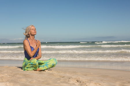 Senior woman meditating while sitting on shore against clear sky at beach