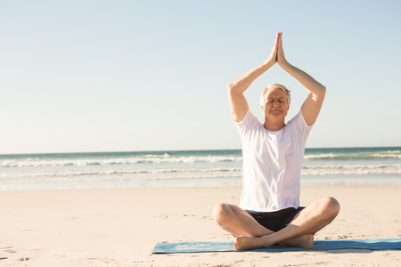 Full length of senior man with eyes closed meditating at beach on sunny day Stock Photo