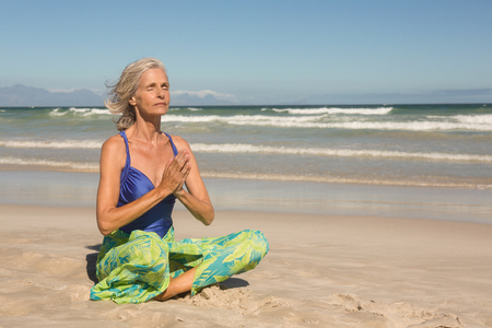 Close up of woman meditating while sitting on shore at beach Stock Photo